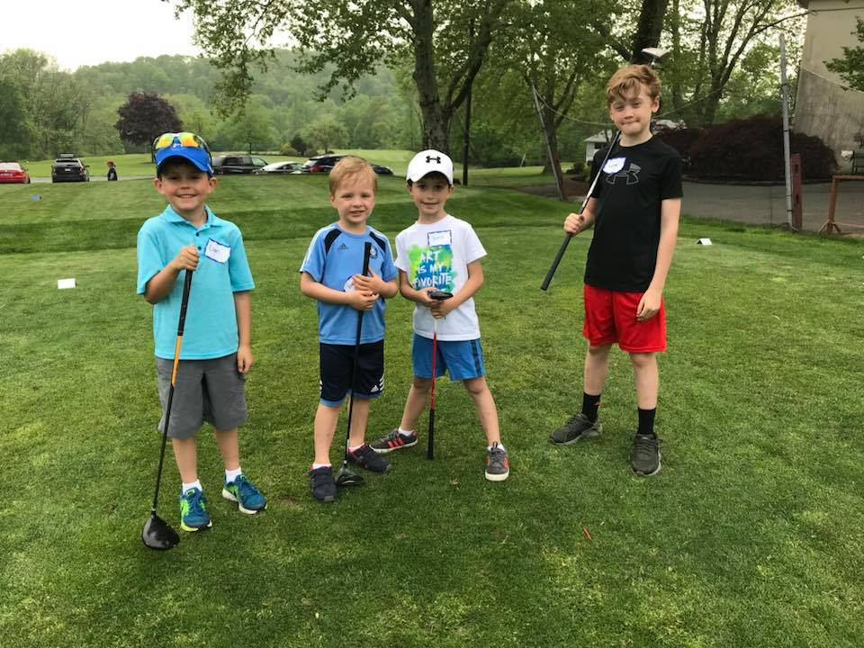 Four boys participating in a junior golf clinic at Manor Golf Club